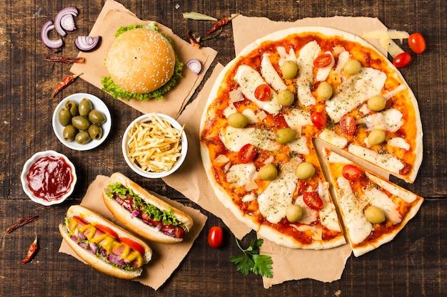 Bovenaanzicht van pizza op houten tafel Gratis Foto