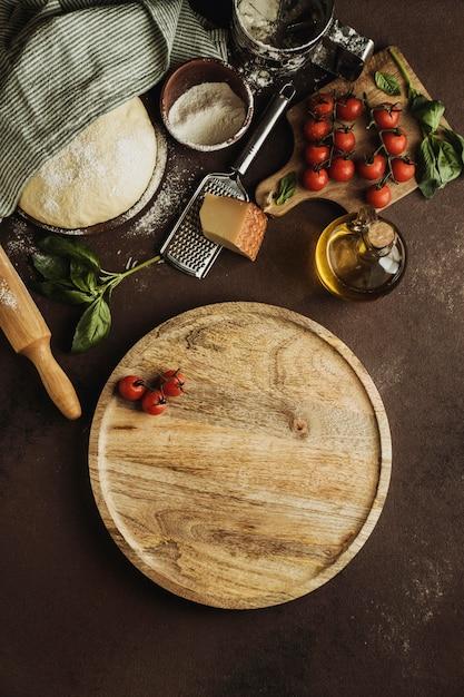Bovenaanzicht van pizzadeeg met houten plank en tomaten Gratis Foto