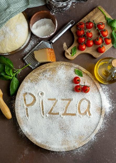 Bovenaanzicht van pizzadeeg met houten plank en woord geschreven in bloem Gratis Foto
