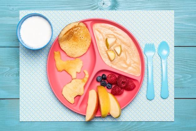 Bovenaanzicht van plaat met babyvoeding en assortiment van fruit Gratis Foto