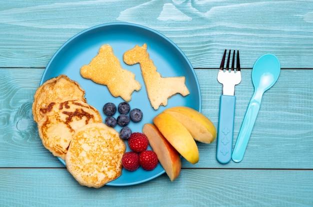 Bovenaanzicht van plaat met fruit en pannenkoeken voor babyvoeding Gratis Foto