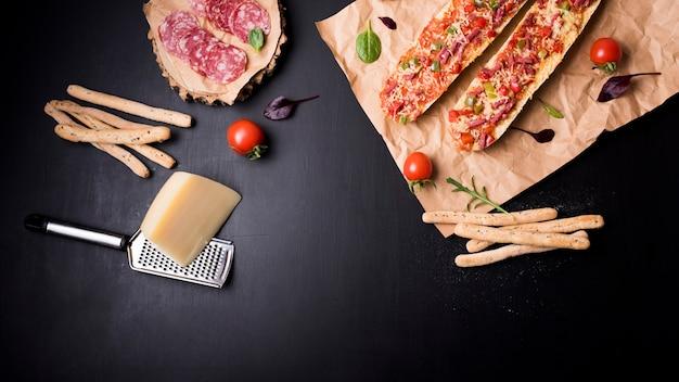 Bovenaanzicht van plakjes pepperoni; brood sticks; kaas; tomaat en baguette pizza op bruin papier over zwart aanrecht Gratis Foto