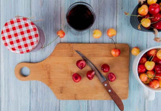 Bovenaanzicht van plakjes rode rijpe kers op een houten snijplank met een keukenmes en regenachtigere kersen glas sap en jam in een glazen pot op rustiek Gratis Foto