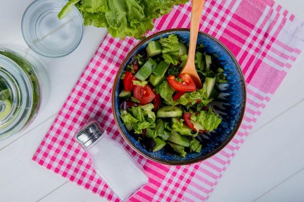 Bovenaanzicht van plantaardige salade en zout op geruite doek met detox water en sla op hout Gratis Foto
