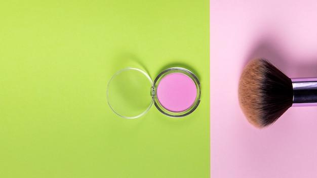 Bovenaanzicht van poeder en penseel op roze en groene achtergrond Gratis Foto