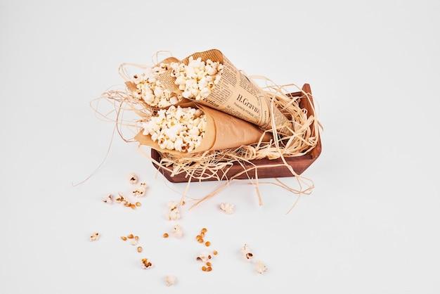 Bovenaanzicht van popcorn verpakt in papier op wit geïsoleerd. Gratis Foto