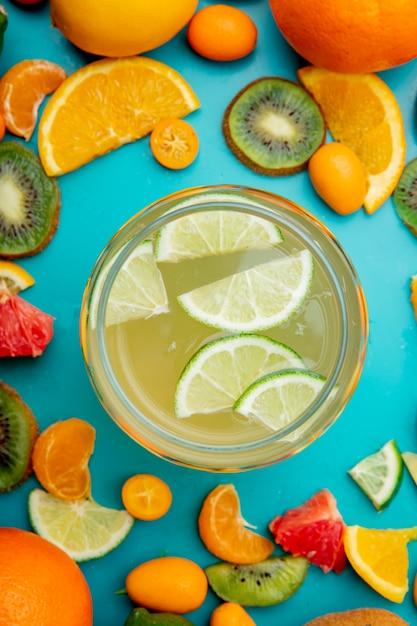 Bovenaanzicht van pot citroensap en citrusvruchten rond op blauw oppervlak Gratis Foto