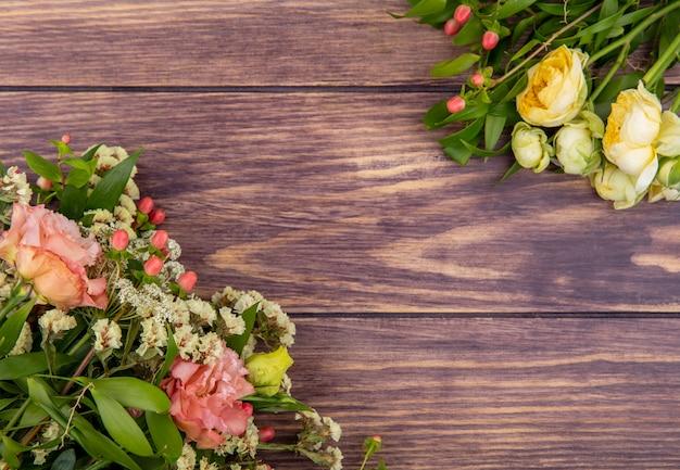 Bovenaanzicht van prachtige en verse bloemen zoals pioenrozen en rozen op een houten oppervlak Gratis Foto