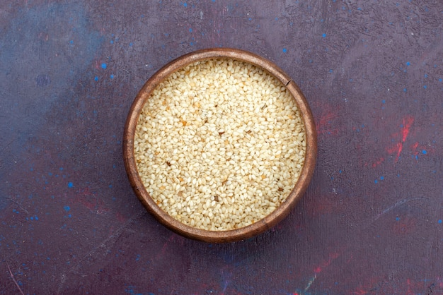 Bovenaanzicht van rauw product in ronde bruine pot op donkere ondergrond Gratis Foto