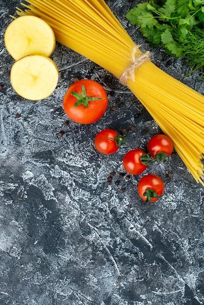 Bovenaanzicht van rauwe pasta met aardappel, peterselie en tomaten op lichtgrijs oppervlak Gratis Foto