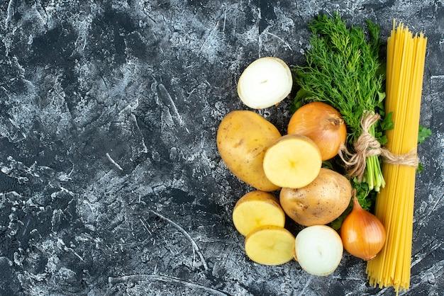 Bovenaanzicht van rauwe pasta met aardappelen, peterselie en uien op lichtgrijs oppervlak Gratis Foto