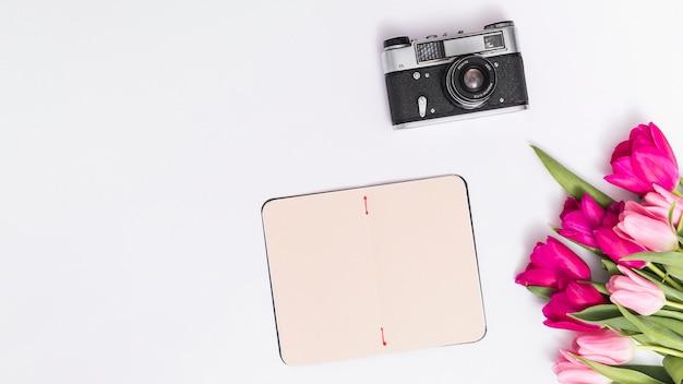 Bovenaanzicht van retro camera; tulp bloemen; en lege kaart tegen witte achtergrond Gratis Foto
