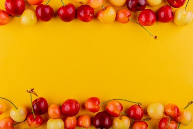 Bovenaanzicht van rijpe rode en gele kersen geïsoleerd op geel met kopie ruimte Gratis Foto