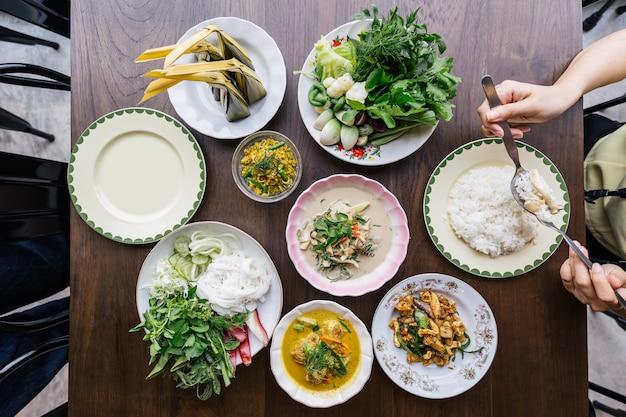 Bovenaanzicht van rijstnoedels met krab-kerriesaus, geserveerd met groenten. roer gebakken pittig gehakt varkensvlees met kruiden. pittige knapperige varkenshuid- en champignonsoep. klassieke thaise keuken met stoomrijst. Premium Foto