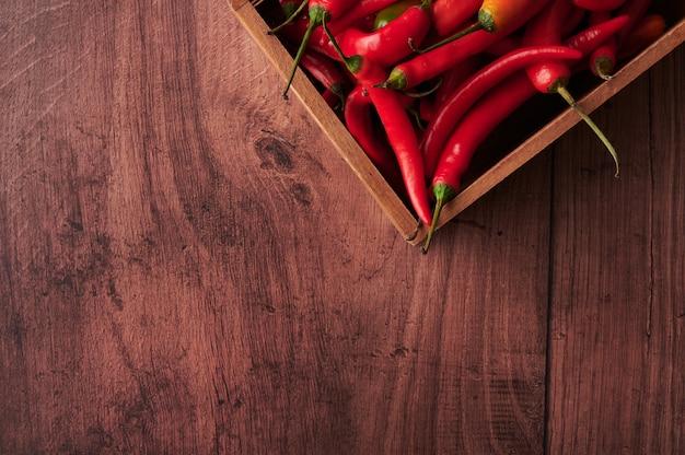 Bovenaanzicht van rode chilipepers in een doos op houten oppervlak met ruimte voor tekst Gratis Foto