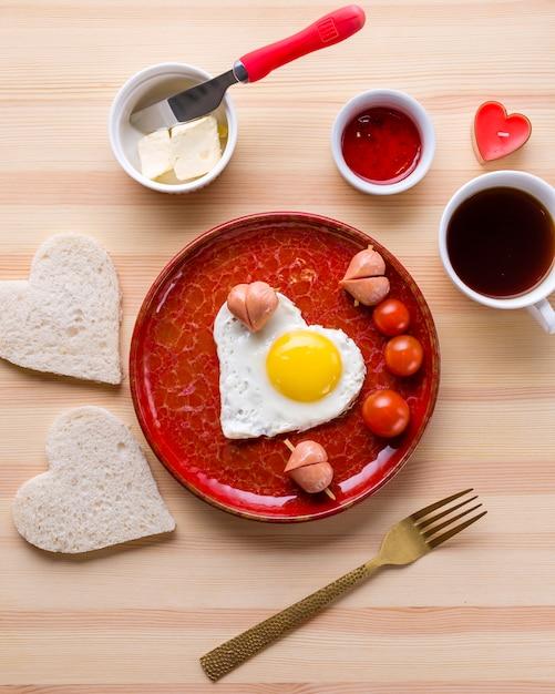 Bovenaanzicht van romantisch ontbijt en hartvormig ei met toast Gratis Foto
