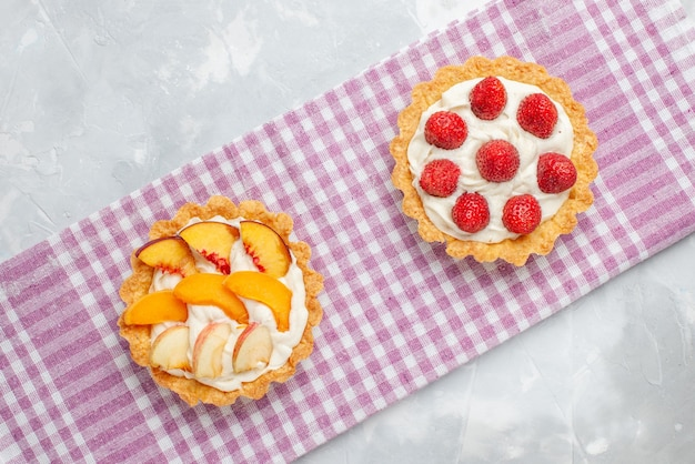 Bovenaanzicht van romige taarten met witte lekkere room en gesneden aardbeien perziken abrikozen op licht bureau, fruitcake room bakken Gratis Foto