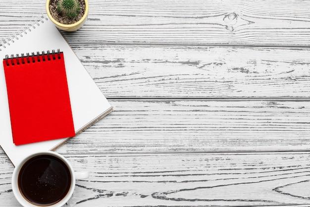 Bovenaanzicht van rommelig wit bureau met lege laptop Premium Foto