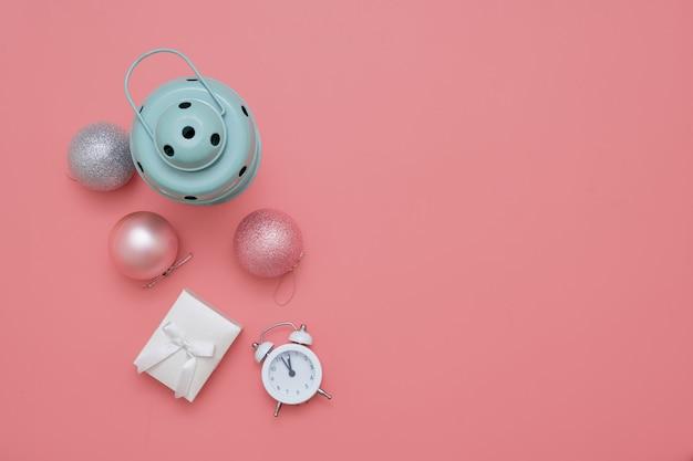 Bovenaanzicht van roze kerstballen en mint lamp op roze achtergrond Premium Foto