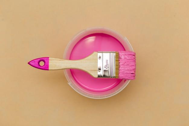 Bovenaanzicht van roze verf en penseel Premium Foto