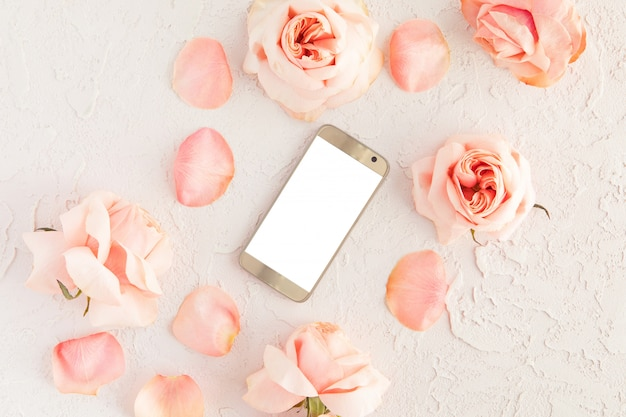 Bovenaanzicht van roze vrouwelijke bureau met moderne gouden mobiele telefoon met wit leeg scherm en bloemen Premium Foto