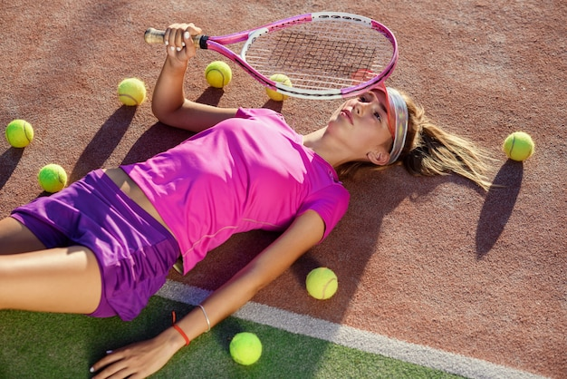 Bovenaanzicht van schattig meisje in de dop liggend op tennisbaan buiten met racket in de hand en veel ballen op de grond na de training. Premium Foto