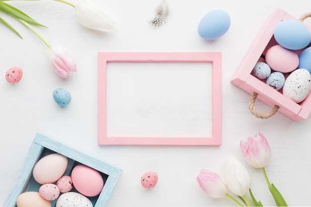Bovenaanzicht van schattige dozen met kleurrijke paaseieren en frame Gratis Foto