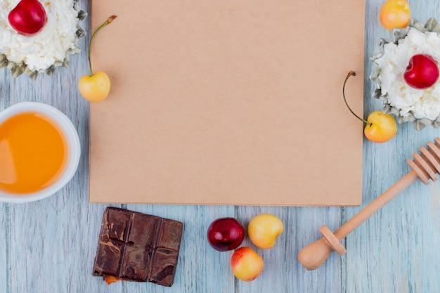Bovenaanzicht van schetsboek en donkere chocolade honing cottage cheese en verse rijpe gele en rode kersen rond gerangschikt op grijs Gratis Foto