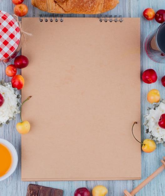 Bovenaanzicht van schetsboek en kwark met verse rijpe gele en rode kersen rond gerangschikt op grijs Gratis Foto