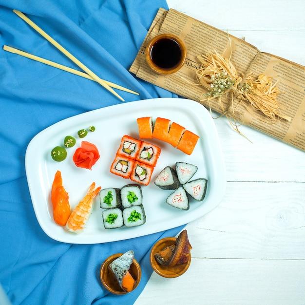 Bovenaanzicht van set sushi en maki met sojasaus op blauw en wit Gratis Foto