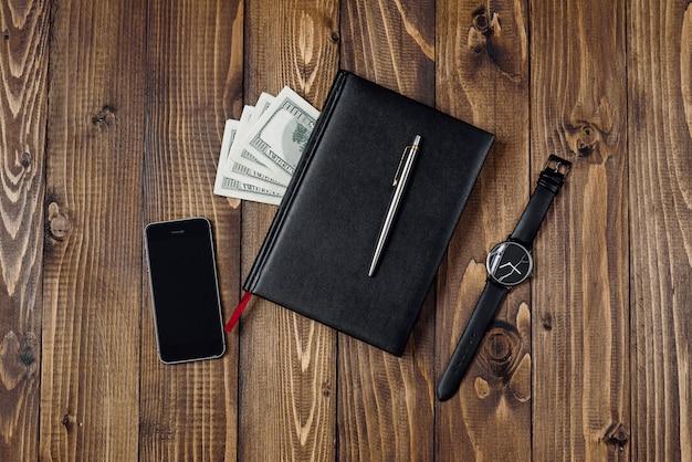 Bovenaanzicht van smartphone, horloge, pen, laptop en geld Premium Foto