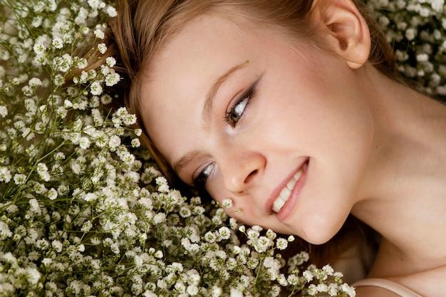 Bovenaanzicht van smiley vrouw poseren met lentebloemen Premium Foto