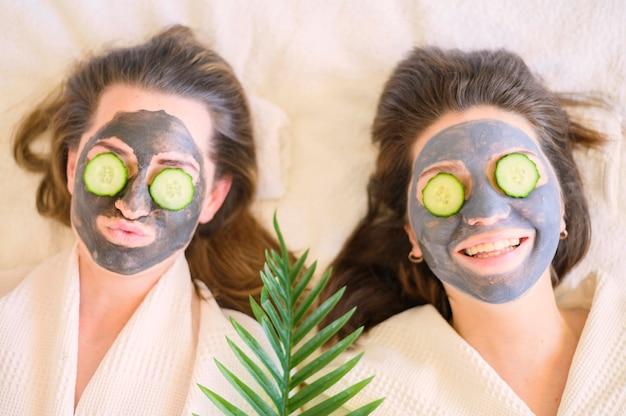 Bovenaanzicht van smileyvrouwen met gezichtsmaskers en plakjes komkommer op hun ogen Gratis Foto