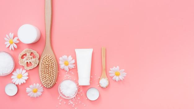 Bovenaanzicht van spa essentials omgeven door kamille bloemen Gratis Foto