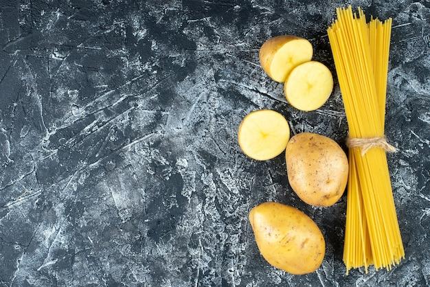Bovenaanzicht van spaghetti met aardappelen op lichtgrijs oppervlak Gratis Foto