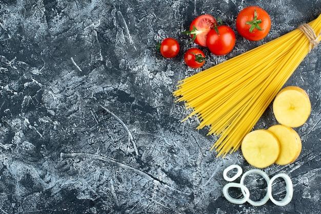 Bovenaanzicht van spaghetti met aardappelen, uienringen en tomaten Gratis Foto