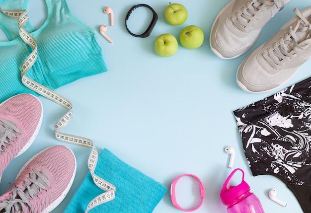 Bovenaanzicht van sport accessoires met kopie ruimte. loopschoenen, beha's, fles, koptelefoon, handdoek, meetlint op blauwe achtergrond Premium Foto