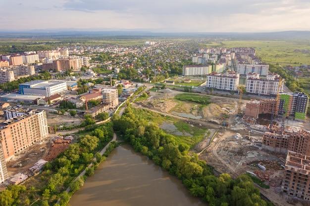 Bovenaanzicht van stedelijke ontwikkelende stadslandschap met hoge flatgebouwen en voorstad huizen Premium Foto