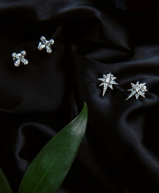Bovenaanzicht van sterling zilveren oorbellen met diamanten met studs op zwarte muur Gratis Foto