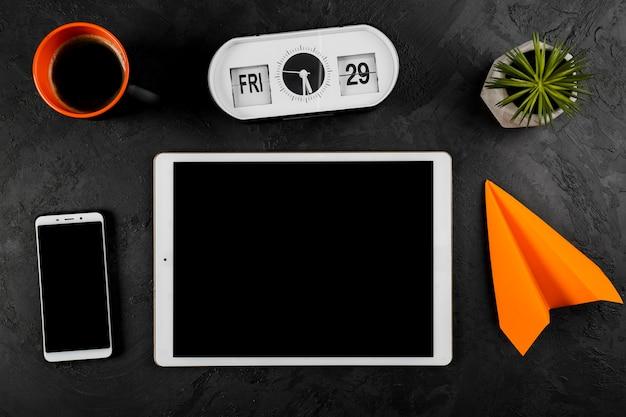 Bovenaanzicht van tablet klok en papier vliegtuig en koffiemok Gratis Foto