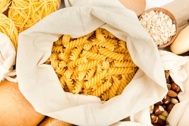 Bovenaanzicht van tas met pasta en assortiment van noten Gratis Foto