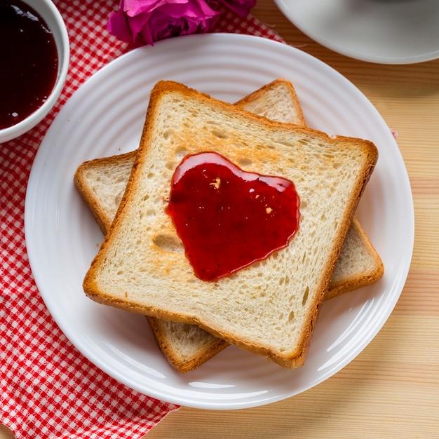 Bovenaanzicht van toast met jam en roos Gratis Foto