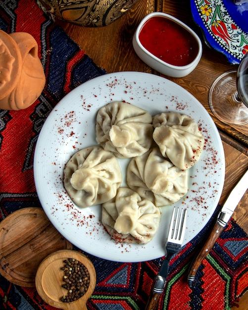 Bovenaanzicht van traditionele georgische khinkaliwith sumakh en pittige saus op een witte plaat Gratis Foto