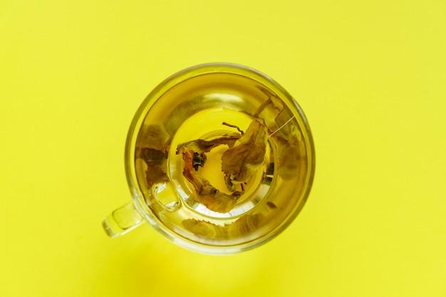 Bovenaanzicht van transparante cup met groene thee op gele achtergrond. Premium Foto