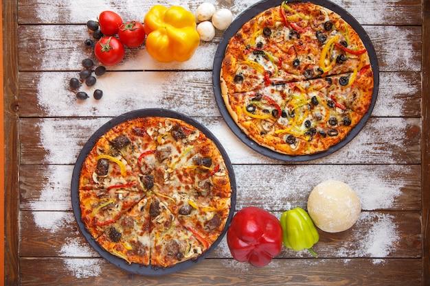 Bovenaanzicht van twee italiaanse pizza's met vlees, paprika, olijven en champignons Gratis Foto