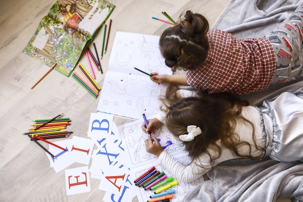 Bovenaanzicht van twee kleine meisjes die tekenen in het kleurboek tot op de vloer op de deken Gratis Foto