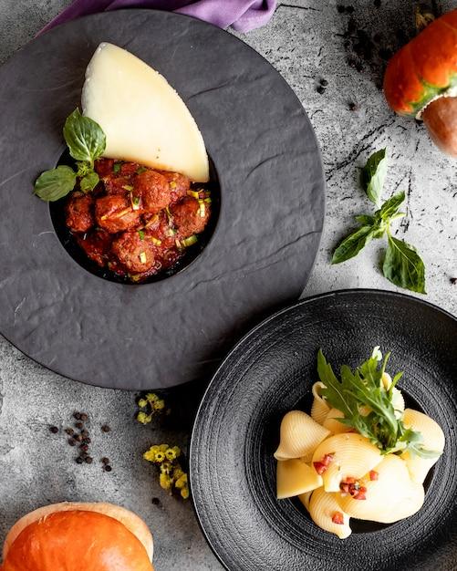 Bovenaanzicht van twee platen met gehaktballetjes in tomatensaus en schelpen pasta Gratis Foto