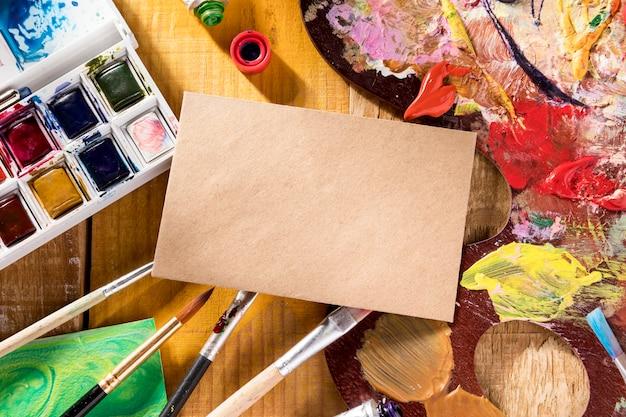 Bovenaanzicht van verf palet met borstels en papier Premium Foto