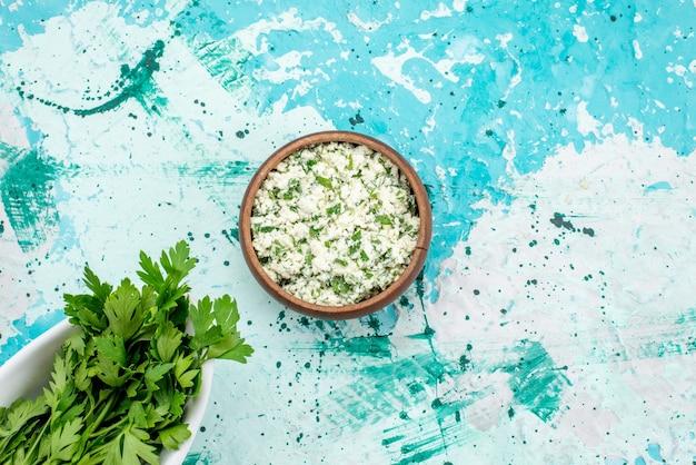 Bovenaanzicht van vers gesneden koolsalade met greens in bruine kom op helderblauwe, groene de versheidssnack van de voedselgroente salade Gratis Foto