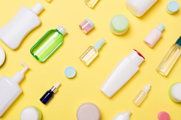 Bovenaanzicht van verschillende cosmetische flessen en container voor cosmetica op geel. plat lag samenstelling met copyspace Premium Foto